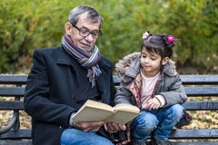 Grandfather and granddaughter in park. Grandfather and granddaughter reading a book in autumn park Royalty Free Stock Photos