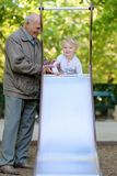 Grandfather with granddaughter on playground Royalty Free Stock Photos