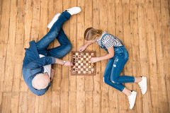 Grandfather and granddaughter playing chess on hardwood floor royalty free stock image