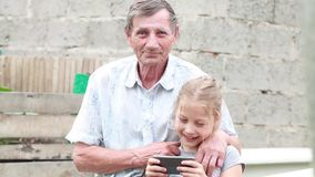 Grandfather and granddaughter playing games on your mobile phone outdoors summer day stock video