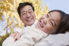 Grandfather and Granddaughter Playing in the Park, Laughing, in Autumn Royalty Free Stock Photography