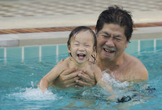 Grandfather with granddaughter in the pool. Stock Images