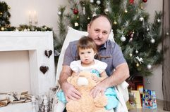 Grandfather and granddaughter portrait in Christmas interior. Little girl sitting behind older father with Teddy bear Royalty Free Stock Photography