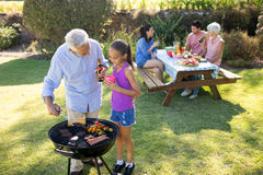 Grandfather and granddaughter preparing barbecue while family having meal Stock Photo