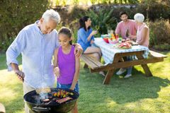 Grandfather and granddaughter preparing barbecue while family having meal. In background royalty free stock image