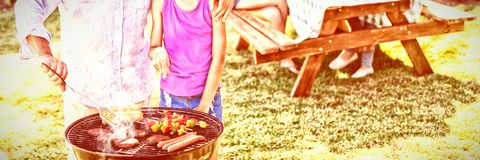 Grandfather and granddaughter preparing barbecue while family having meal. In background stock photos