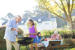Grandfather and granddaughter preparing barbecue for their family. In the park Royalty Free Stock Photography