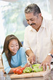 Grandfather And Granddaughter Preparing meal Stock Photo