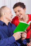 Grandfather and granddaughter reading book Stock Photos