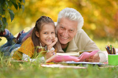 Grandfather and  granddaughter reading book Royalty Free Stock Images