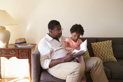 Grandfather And Granddaughter Reading Book At Home Together Stock Images