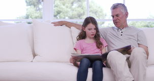 Grandfather and granddaughter reading book on sofa stock video footage