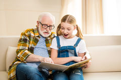 Grandfather and granddaughter reading book together at home Stock Photo