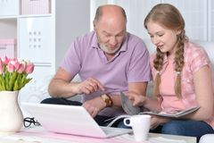 Grandfather and granddaughter reading magazine. With laptop on table nearby Stock Photos