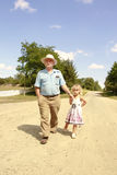 Grandfather and granddaughter are on the road Royalty Free Stock Image