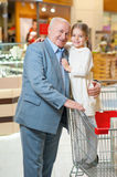 Grandfather with granddaughter at the shop. Love you granddad. Happy and smiling grandfather with granddaughter are hugging each other at the shop royalty free stock photography