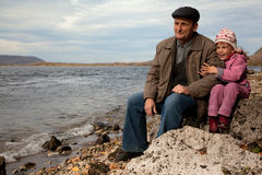 Grandfather and granddaughter sit near lake Royalty Free Stock Image