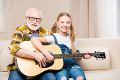 Grandfather and granddaughter sitting on sofa with guitar and smiling at camera. Happy grandfather and granddaughter sitting on sofa with guitar and smiling at Stock Photos