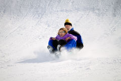 Grandfather Granddaughter Sledding. A grandfather and his granddaughter ride a sled down a snowy slope. There is snow flying off the front of the sled and they Stock Images