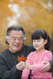 Grandfather and granddaughter smiling and looking at leaf together Royalty Free Stock Photo