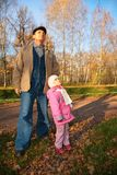Grandfather with  granddaughter stand in park in a Stock Image