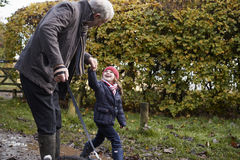 Grandfather And Granddaughter Taking Dog For Walk Royalty Free Stock Photography