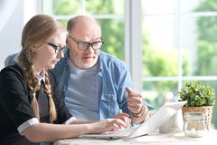 Grandfather and granddaughter using laptop. Together at home Royalty Free Stock Photo