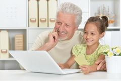 Portrait of grandfather and granddaughter using laptop together stock photography