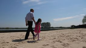 Grandfather and granddaughter walk on the beach along the lake. 4K Slow Mo. Grandfather and granddaughter walk on the beach along the lake stock footage