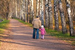 Grandfather with granddaughter walk in park. In autumn Stock Photography