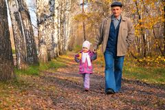 Grandfather with granddaughter walk in park royalty free stock photos