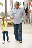 Grandfather With Granddaughter Walking Along Street Stock Photo