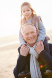 Grandfather And Granddaughter Walking On Winter Beach Stock Images