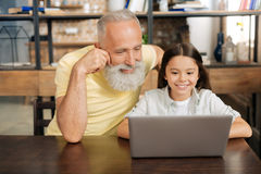 Grandfather and granddaughter watching cartoons on laptop. Quality time. Pleasant elderly men and sitting at the table next to his little granddaughter and royalty free stock photos