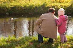 Grandfather with granddaughter in wood in autumn l. Behind Grandfather with granddaughter in wood in autumn look on ducks in water Stock Photos