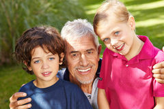 Grandfather with grandkids in garden Stock Photography