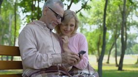 Grandfather and grandmother admiring children photos in smartphone application