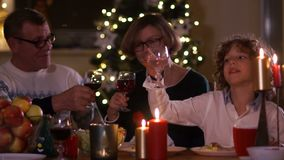 Grandfather and grandmother are drinking red wine while sitting at the holiday table. Christmas toast, Christmas wishes. Happy family stock footage