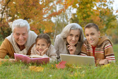 Grandfather, grandmother and grandchildren in park. Happy grandfather, grandmother and grandchildren doing homework in park royalty free stock image