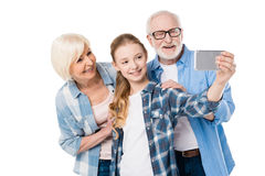 Grandfather, grandmother and granddaughter taking selfie together. Isolated on white Stock Image