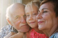 Grandfather and grandmother holding granddaughter stock photos