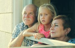 Grandfather and grandmother holding granddaughter stock images