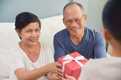 Grandfather and Grandmother receiving red gift box. Royalty Free Stock Photography