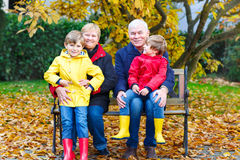 Grandfather, grandmother and two little kid boys, grandchildren sitting in autumn park. Stock Image