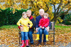 Grandfather, grandmother and two little kid boys, grandchildren sitting in autumn park. Happy family enjoying time together. Friends, love, relationship Royalty Free Stock Images