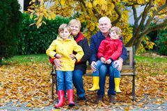 Grandfather, grandmother and two little kid boys, grandchildren sitting in autumn park. Happy family enjoying time together. Friends, love, relationship royalty free stock photo
