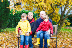 Grandfather, grandmother and two little kid boys, grandchildren. Sitting in autumn park. Happy family enjoying time together. Friends, love, relationship Royalty Free Stock Photos