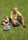 Grandfather and grandson. Working on laptops Stock Photography