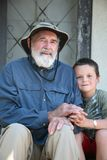 Grandfather and grandson. Elderly grandfather with his grandson sitting on a home porch Stock Images