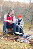Grandfather and grandson around a campfire Stock Photos